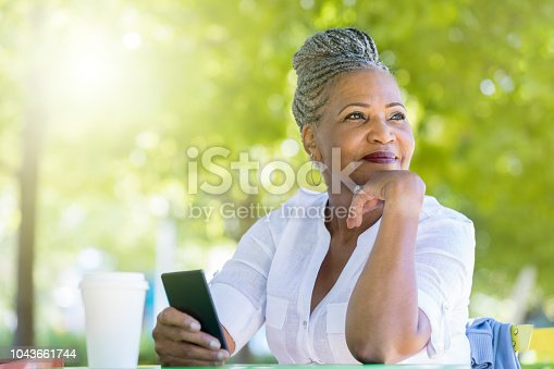A cheerful senior woman rests her chin in her hand as she looks away.  She is sitting at a table in a public park with coffee and her smart phone and waiting for a friend.