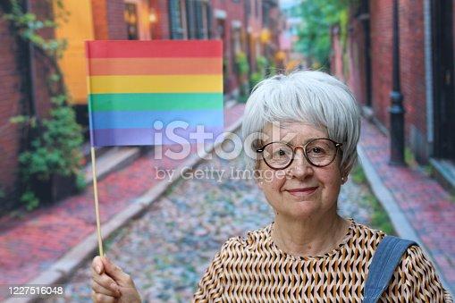 Senior woman waiving the rainbow flag.