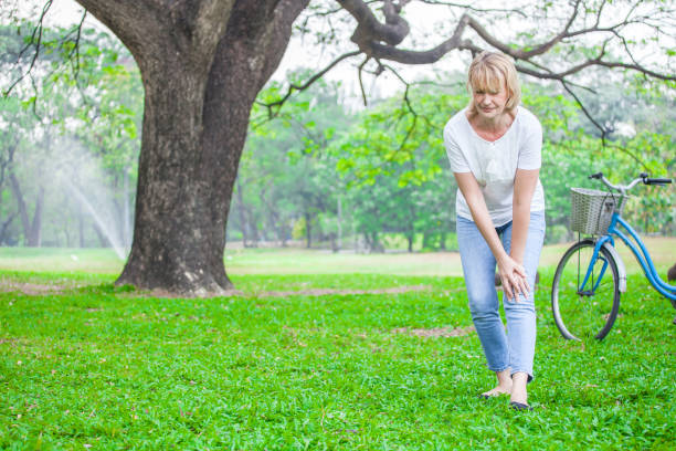 Senior woman walking in autumn park and having knee pain. Arthritis pain concept. stock photo