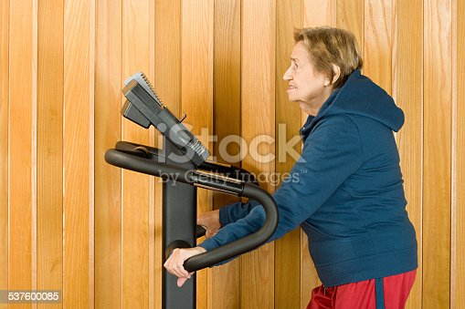 istock Senior woman walking on a treadmill 537600085