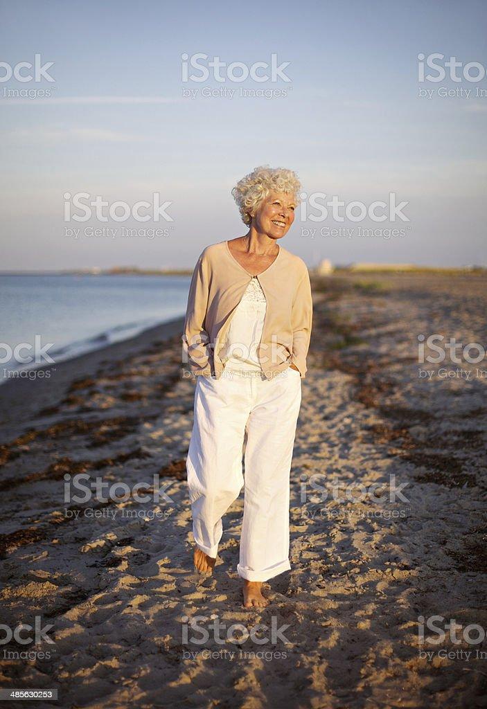 Senior woman walking on the beach stock photo