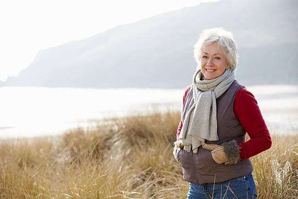 senior mujer caminando a través de las dunas de arena en la playa de invierno - mujeres mayores fotografías e imágenes de stock