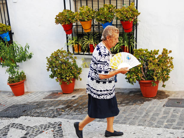 Senior woman walking with a fan in her hand stock photo