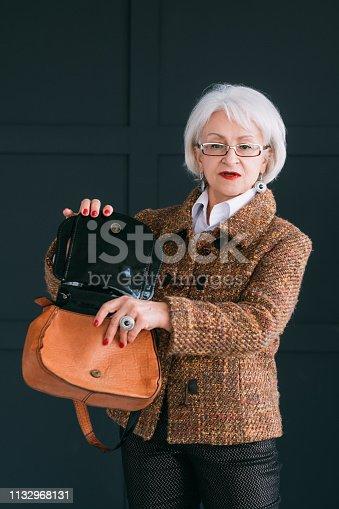 1133515238 istock photo senior woman wardrobe style fashion shopping bag 1132968131