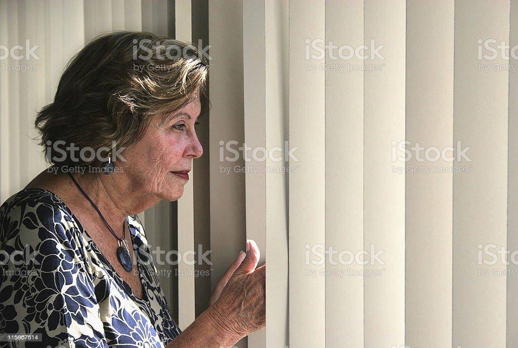 Senior woman watching through the window royalty-free stock photo