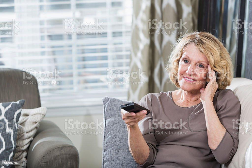 Senior woman watching tv in living room stock photo