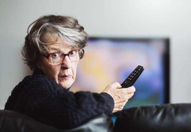 ältere frau, die vor dem fernseher dreht sich erschrocken und gereizt - alte serien stock-fotos und bilder