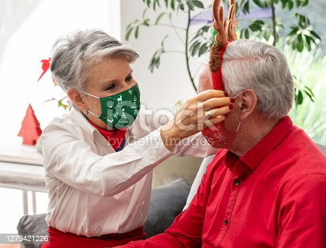 Portrait of a senior woman wearing a facemask while putting reindeer ears on her husband at Christmas time - holidays concepts