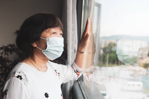 Senior woman wearing a mask and looking through the window stock photo