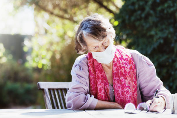Senior woman wearing a mask to avoid infection during the COVID-19 coronavirus epidemic stock photo