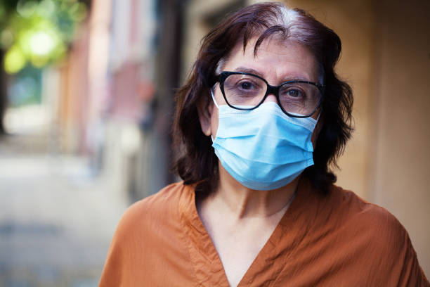Senior woman wearing a protective face mask and eyeglasses stock photo