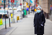 Senior Korean woman wearing a surgical mask on the streets of New York City.
