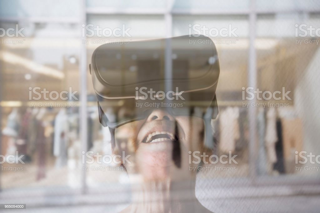Senior woman wearing a virtual reality headset and enjoying virtual reality shopping stock photo