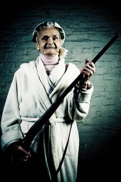 Senior Woman Wearing Curlers and Holding Shotgun stock photo