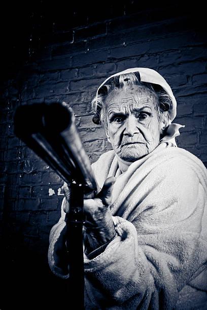 Senior Woman Wearing Curlers and Holding Shotgun, Toned stock photo