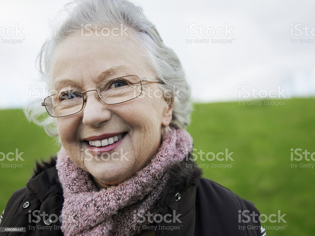 Senior Woman wearing glasses and smiling to camera stock photo