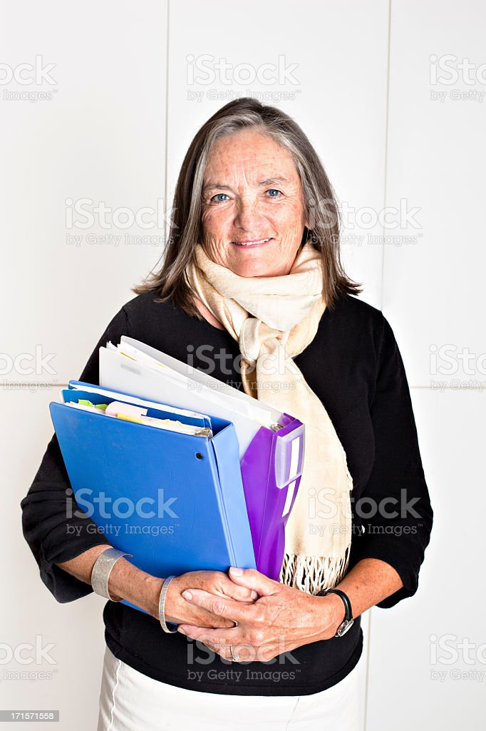 Senior woman wearing scarf holding documents royalty-free stock photo