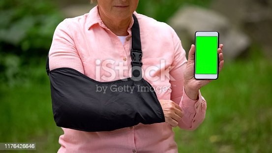 istock Senior woman wearing shoulder immobilizing sling showing smartphone green screen 1176426646