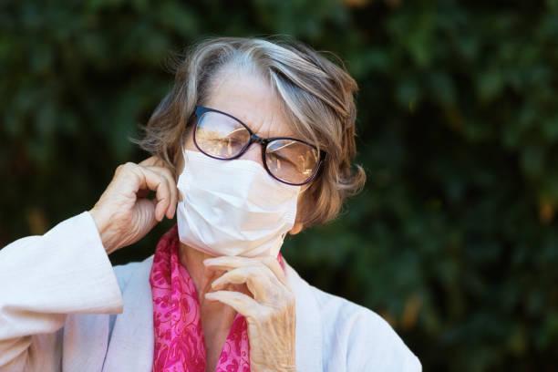 Senior woman wearing surgical mask during COVID-19 coronavirus epidemic stock photo