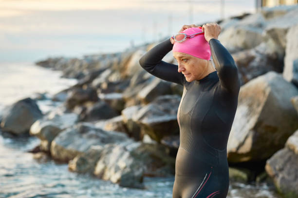 Senior woman wearing swimming goggles at beach Senior woman wearing swimming goggles at beach. Female is preparing to swim against rocks. Swimmer in wetsuit is looking away. wetsuit stock pictures, royalty-free photos & images