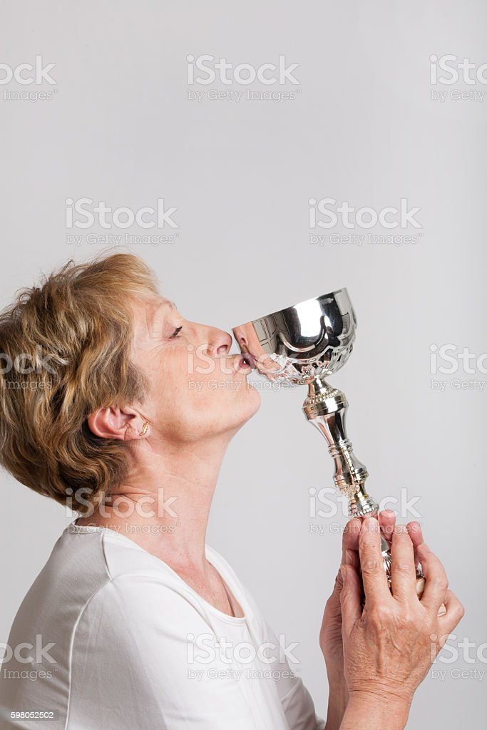 femme sénior qui embrasse son trophée stock photo