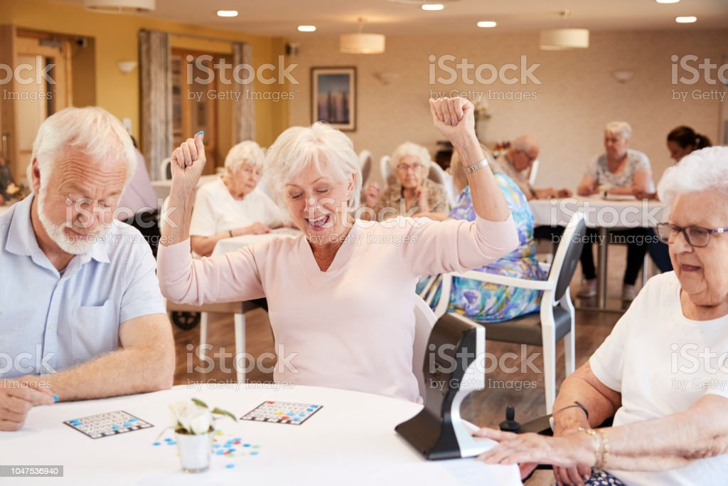 Senior Woman Winning Game Of Bingo In Retirement Home stock photo