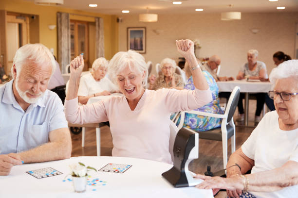 senior woman winning game of bingo in retirement home - game of life stock photos and pictures