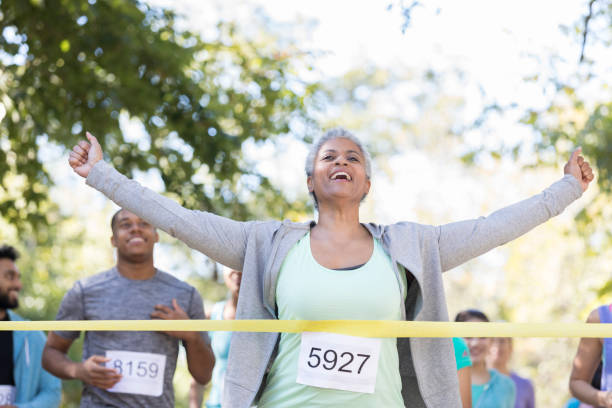 ältere frau gewinnt ein charity race - laufveranstaltungen stock-fotos und bilder
