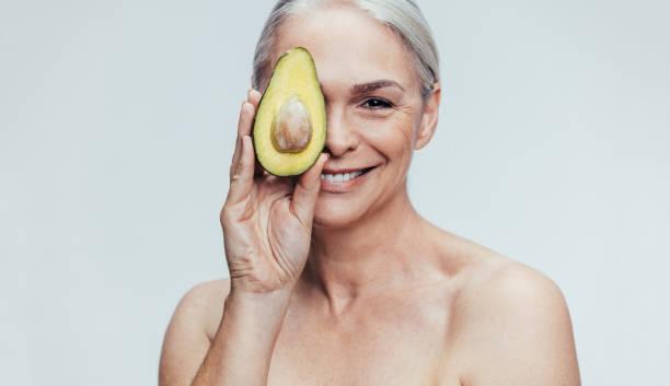 senior kvinna med en halv avokado - mature women studio grey hair bildbanksfoton och bilder