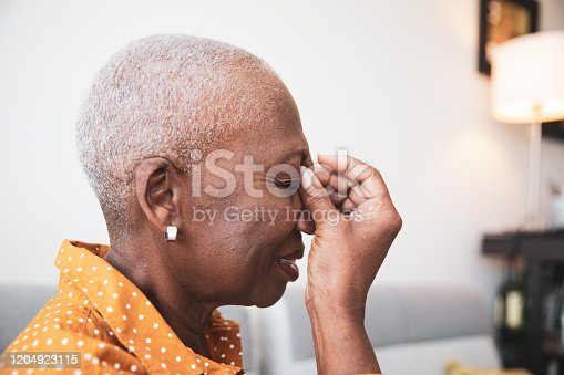 senior African descent woman holding her head in pain