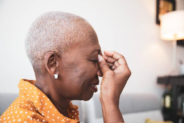 hogere vrouw met een hoofdpijn - bijholte stockfoto's en -beelden