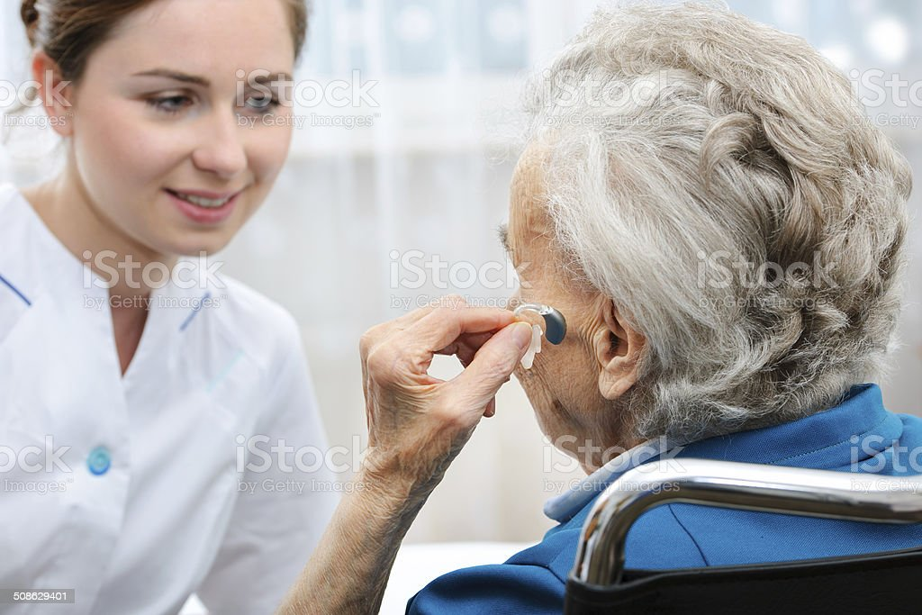 Senior woman with a hearing aid stock photo