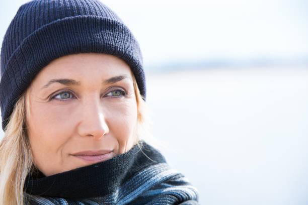 ältere frau mit einer mütze im winter - mützenschal stock-fotos und bilder