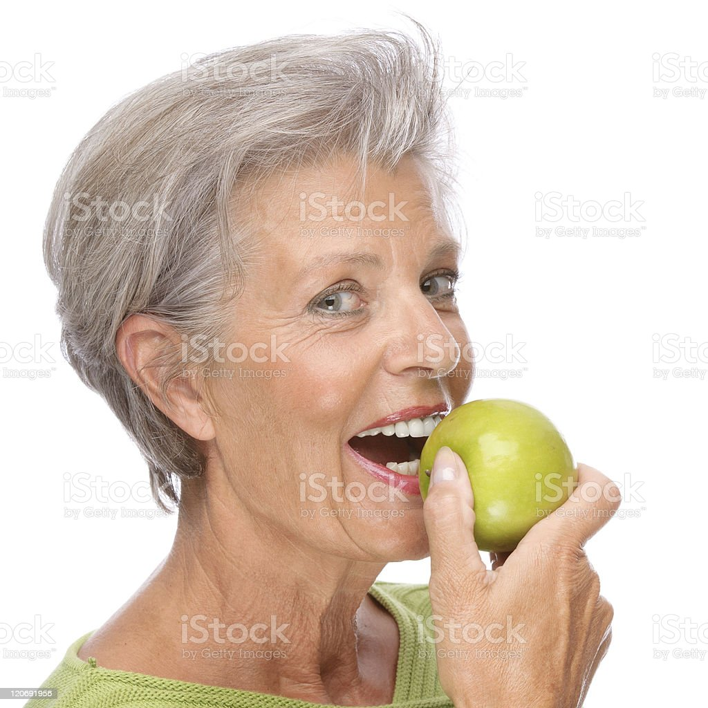 Senior woman with apple royalty-free stock photo