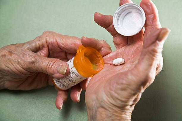senior woman with arthritis holding prescription medicine pill bottle stock photo