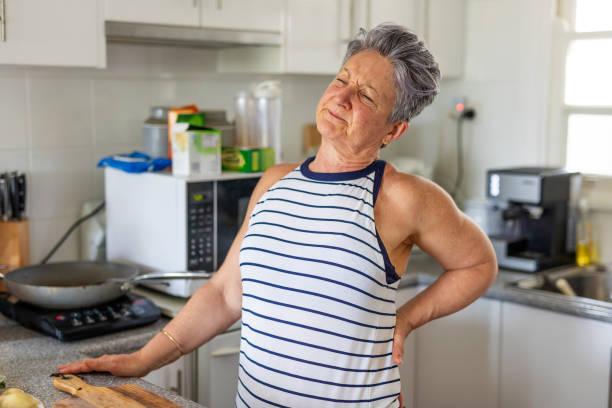 senior kvinna med ryggont i köket - kronisk sjukdom bildbanksfoton och bilder