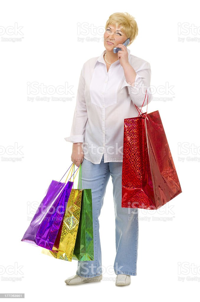 Senior woman with bags and mobile phone royalty-free stock photo