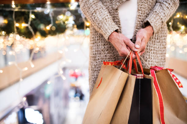 senior woman with bags doing christmas shopping. - shopping stock photos and pictures