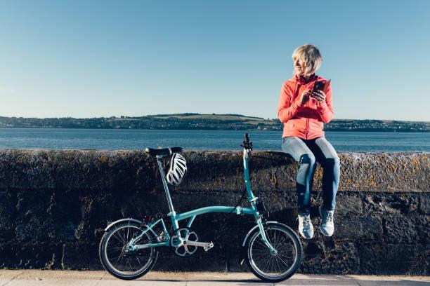 ältere frau mit fahrrad und telefon. - zusammenklappbar stock-fotos und bilder