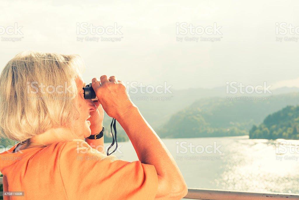 Senior woman with binoculars stock photo