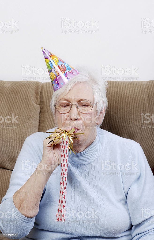 senior woman with birthday hat blowing noise maker royalty-free stock photo