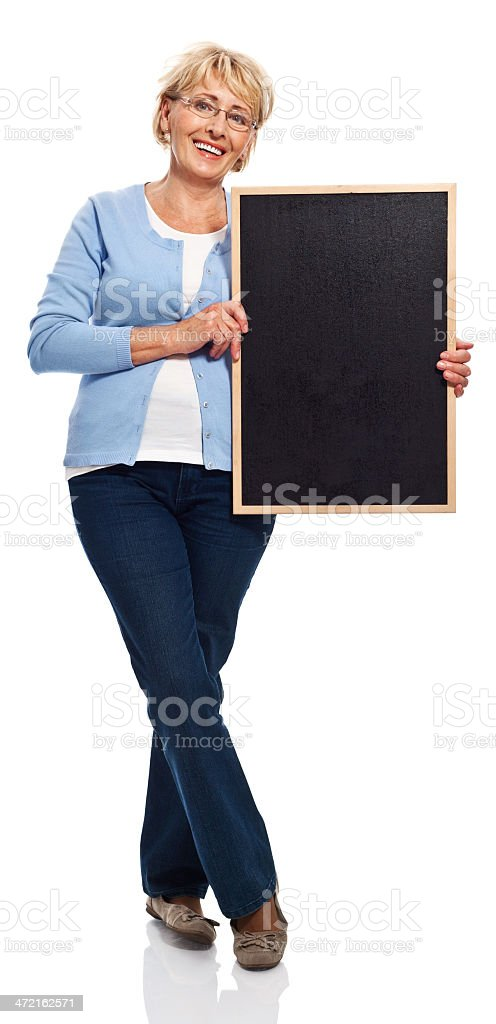 Senior woman with blackboard Full lenght portrait of happy senior woman holding a blackboard in hands and smiling at camera. Studio shot, white background. 60-69 Years Stock Photo