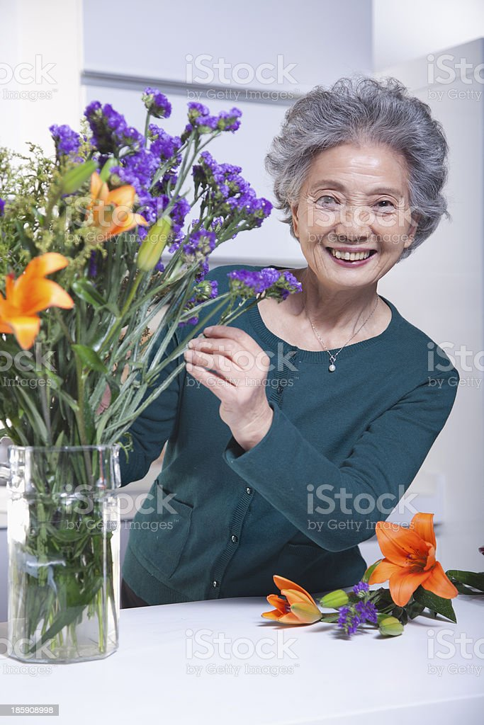 Senior Woman with Bouquet of Flowers in Kitchen, Portrait royalty-free stock photo