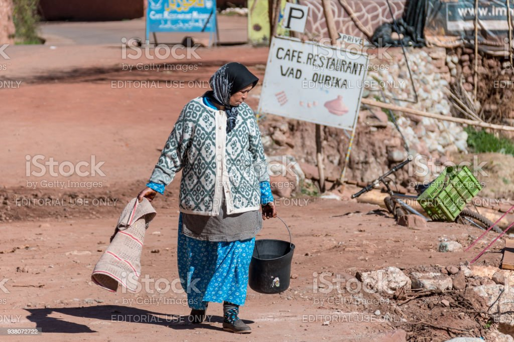 Senior woman with bucket in Berber village, Atlas Mountains, Morocco stock photo