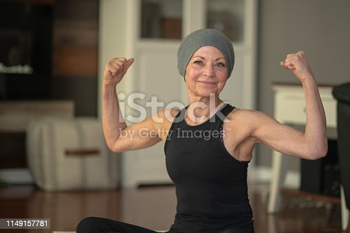 A senior woman with cancer flexes her muscles while sitting at home on her floor. She is smiling because she is getting stronger.