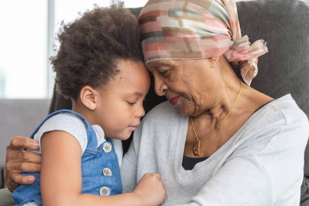senior woman with cancer lovingly holds granddaughter - cancer patient stock pictures, royalty-free photos & images