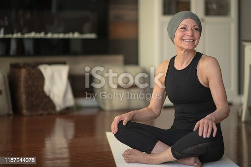 A senior woman with cancer does yoga at home in her living room. She is wearing black active wear.