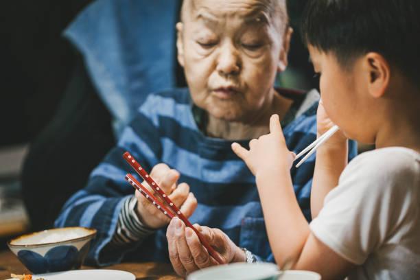 Uma mulher idosa com câncer r tendo refeição com o grande filho na sala de jantar - foto de acervo