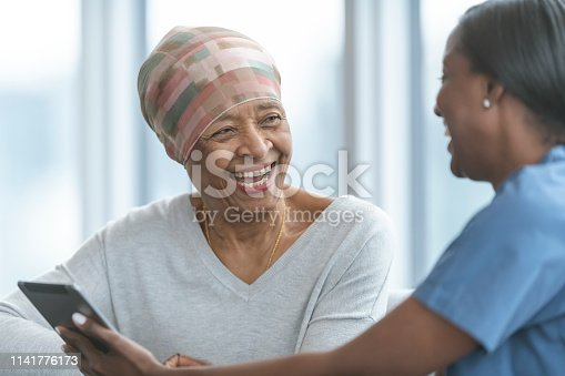 istock Senior woman with cancer reviews test results with female doctor 1141776173