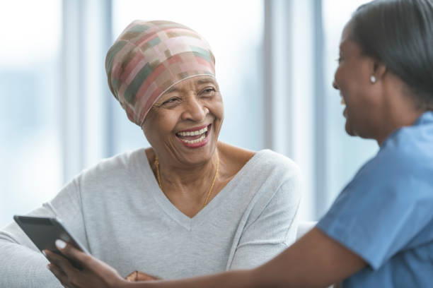 Senior woman with cancer reviews test results with female doctor A woman with cancer is meeting with her doctor. Both individuals are of African descent. The doctor is showing the patient test results on an electronic wireless tablet. They both smile as the doctor gives good news regarding the patient's treatment. cancer patient stock pictures, royalty-free photos & images